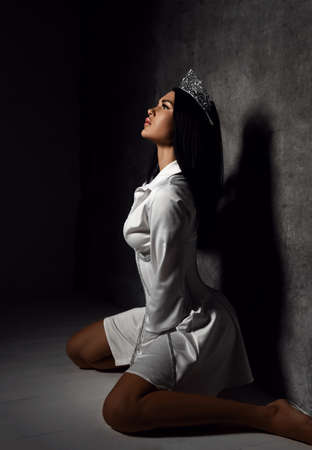 Sensual gorgeous woman with pouty lips in crown and white corset mini dress with chain trim sits on her knees at grey wall posing and looks up at ray of light. Beauty, fashion, trendy outfit.