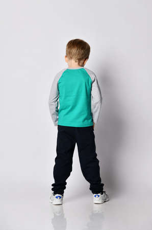 Punished sad blond kid boy in grey sweatshirt, black sport pants and white sneakers stands back to camera and looks down holding hands in his pockets Imagens