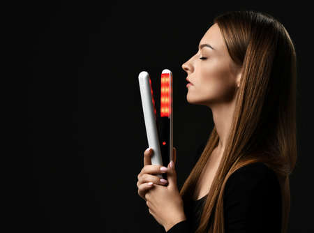 Profile of young pretty woman model with long straight hair standing holding hair straightener in hands with eyes closed over black, copy space. Hairstyle, hairsalon, hairdresser concept
