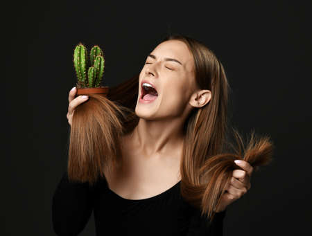 Panicked screaming woman with long silky straight hair compares hair split ends with cactus plant in pot she holds