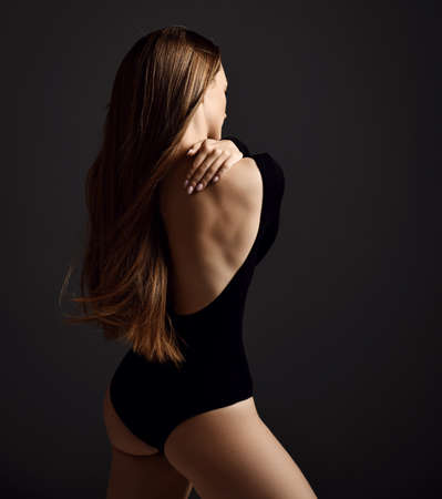 Young sensual slim woman with long silky hair in black bodysuit stands back to camera holding hand at her shoulder