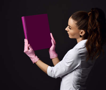 Woman doctor gynecologist reproductologist in pink latex gloves and uniform standing and holding purple album