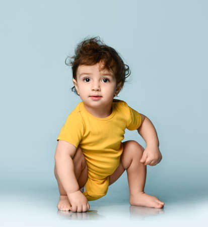 Cute smiling curly baby boy toddler in yellow comfortable jumpsuit sitting on floor and looking at camera