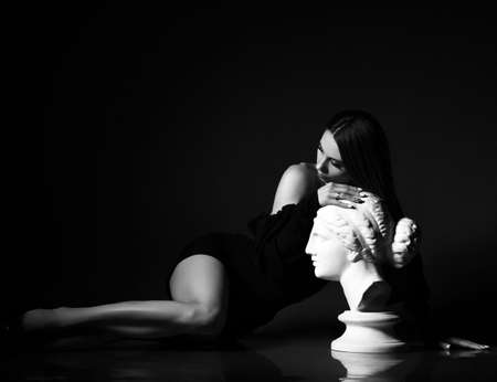 Black and white portrait of sensual slim woman in black tight dress lying on floor leaning on sculpture profile