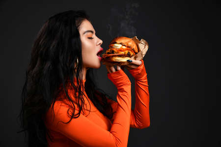 Portrait of hot brunette woman with pouty lips in red clothes eating biting big tasty craft burger with steam