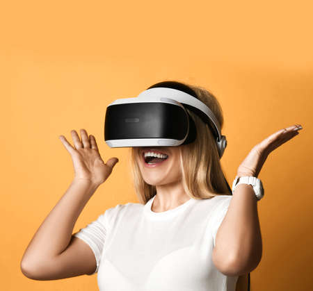 Portrait of happy screaming blonde woman in white t-shirt using VR glasses exploring augmented reality holding hands up