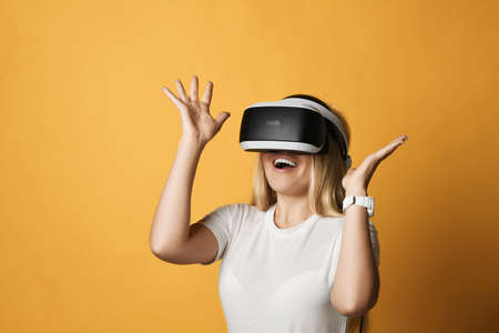 Excited happy screaming blonde woman in white t-shirt uses VR glasses exploring augmented reality holding hands up