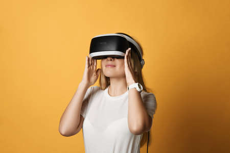 Portrait of young blonde woman in white t-shirt VR glasses technology advanced user operating in augmented reality