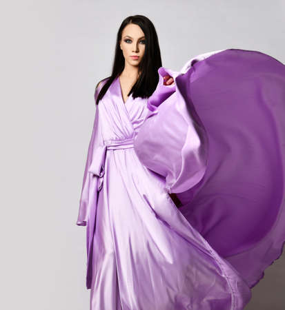 Portrait of graceful brunette woman in lilac evening maxi dress silk gown stands with the hem fluttering in the wind