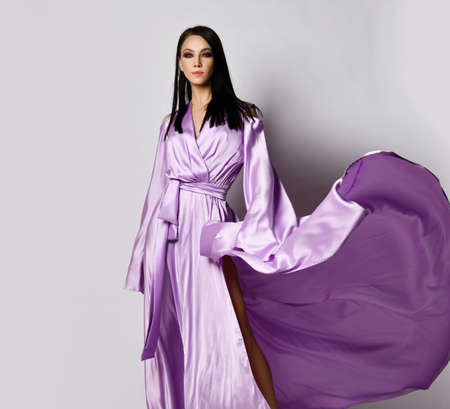 Young pretty gorgeous brunette woman in mauve long maxi dress silk gown stands with the hem fluttering in the wind
