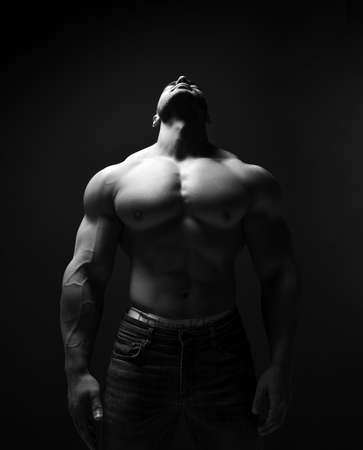 Black and white portrait of handsome muscular man, athlete with perfect built body stands with head thrown back