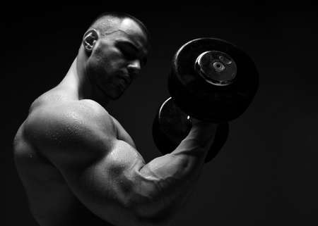 Portrait of muscular men, bodybuilder working out, lifting dumbbell, doing exercises for biceps looking at it