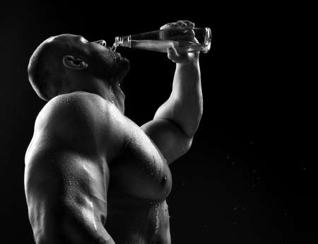 Young muscular build man silhouette drinking water from the bottle after running or after workout outdoors, fitness Stock Photo
