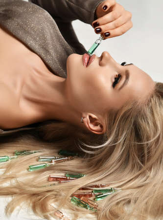 Beautiful blonde girl holding cosmetic ampoules for hair beauty. Young woman with luxurious long healthy hair lying on a floor Standard-Bild