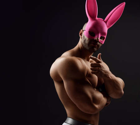 Naked shirtless muscular man wearing pink rabbit mask stands sideways showing biceps and pointing with finger at camera