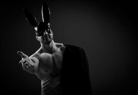 Naked muscular man in black rabbit mask and with jacket on shoulder stands with his arm outstretched to camera Imagens