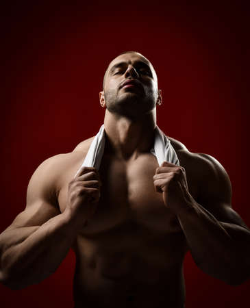 Strong muscular unshaved man, bodybuilder stands with head up and chest holding shirt or towel around his neck