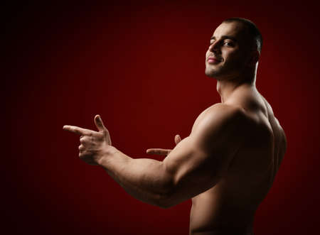 Side view of smiling strong muscular man, bodybuilder standing with chest shirtless pointing fingers aside