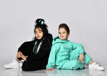 Happy smiling kids girl in black hoodie and pants and boy in modern green, mint color sportswear are sitting on floor