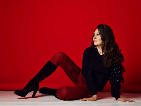 Brunette woman in red and black clothes on floor. Red background.