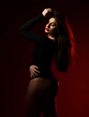 Young romantic slim brunette woman in black bodysuit stands sideways with head turned at camera showing her silhouette