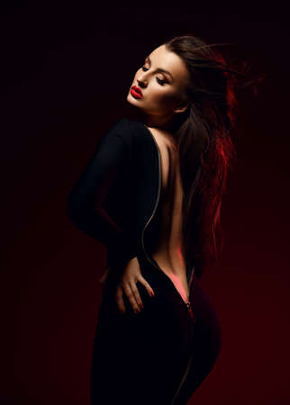 Seductive woman stands sideways in black tight unzipped dress demonstrating her back, waistline and butt