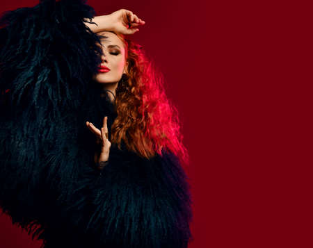 Gorgeous rich young woman with red curly hair wearing luxury fur coat is posing with eyes closed, arm at head over red