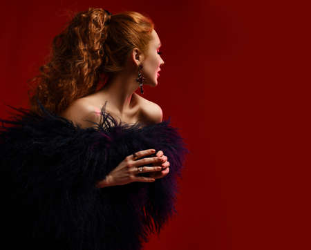 Gorgeous rich young woman with red curly hair wearing luxury fur coat over body standing sideways, turned away