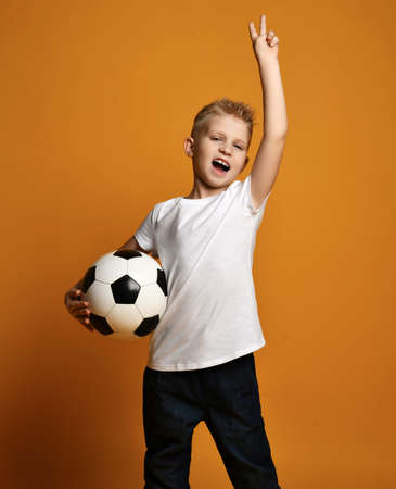 Screaming loudly blonde kid boy in white blank t-shirt stands holding soccer ball in hand and gestures V victory sign