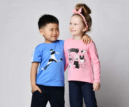 Little cute Asian boy and blonde Caucasian girl in summer clothing best friends stand together hugging