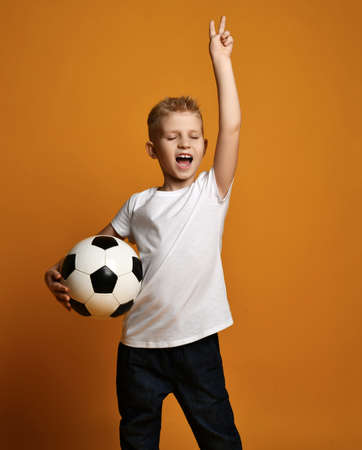 Happy kid boy in white blank t-shirt stands holding soccer ball in hand and gestures V victory sign, celebrates win