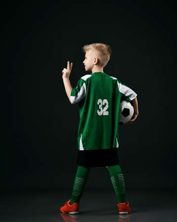Soccer school student, teenager boy in red white striped uniform stands back to camera holding ball and gesturing V sign