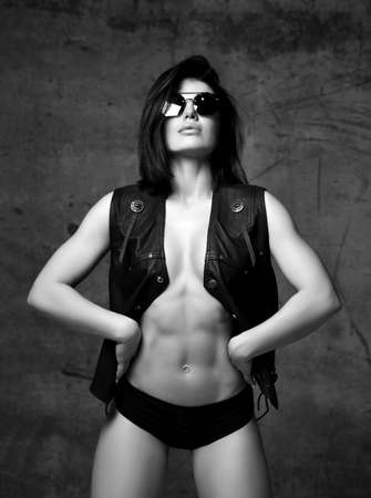 Black and white. Young woman in open black leather jacket on body and panties stands showing her perfect body Reklamní fotografie