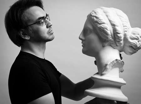 Black and white portrait of adult man in black t-shirt holding in hands, looking at antique sculpture woman head