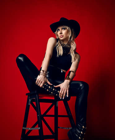 Impudent blonde woman in black leather pants, top and stetson hat sits on stepladder holding her feet in hand Reklamní fotografie