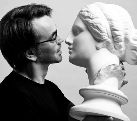 Black and white portrait of adult man in black t-shirt holding in hands antique sculpture woman head, going to kiss it