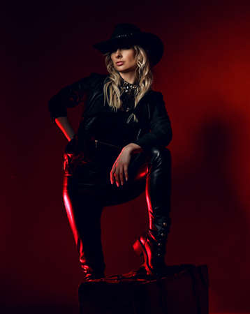 Cool curly blonde woman cowgirl in black leather pants and wide-brimmed stetson hat stands with her foot on chair