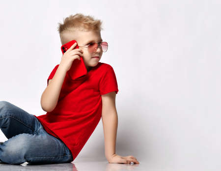 Stylish kid boy child in red t-shirt, jeans, sneakers and sunglasses sitting on floor talking on smartphone looking away Stok Fotoğraf