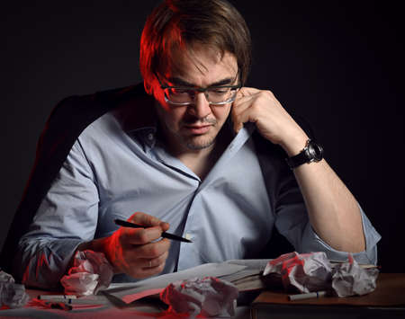 Tired adult man in shirt, jacket and glasses at work, sits behind desk, table with books and sheets and crumpled paper