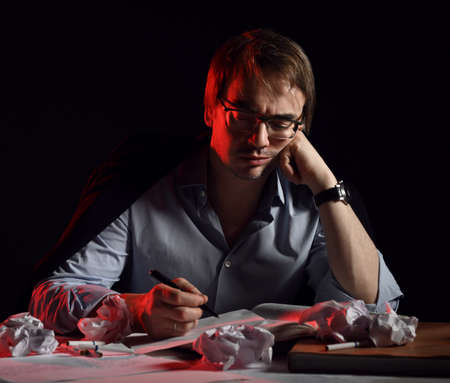 Bored adult man in shirt sits behind desk, table with books and sheets and crumpled paper, correcting materials, writing