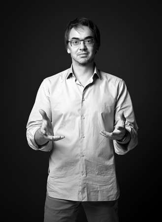 Black and white portrait of unshaved adult man in shirt and jeans standing holding out hands to us, palms up Stok Fotoğraf