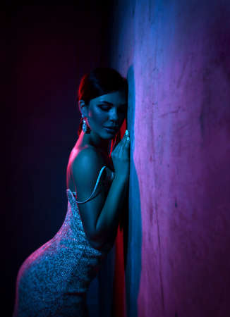 Excited young adult woman in silver tight cocktail dress is standing leaning at concrete wall in neon light