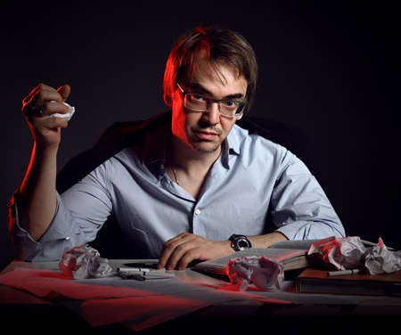 Unshaved mad man in shirt, jacket and glasses sits behind desk, table with books and sheets and crumpled paper in fist