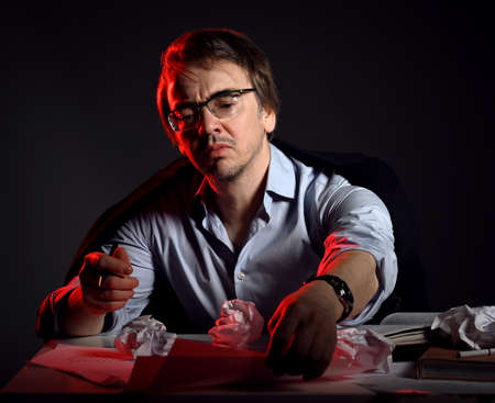 Unshaved man in shirt, jacket and glasses at work, sits behind desk, table with books and sheets and crumpled paper