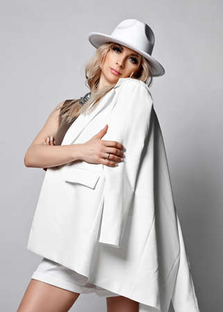 Rich blonde woman in white wide-brimmed  hat and shorts stands showing, demonstrating her white jacket