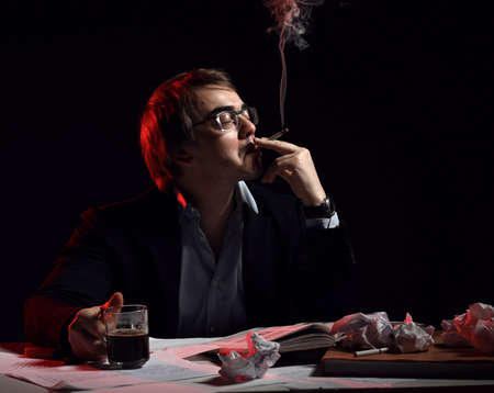 Adult man in shirt and jacket sits behind desk, writing table with book and papers, drinks tea, coffee and smokes Stok Fotoğraf
