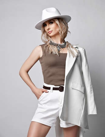 Self-confident wealthy blonde woman in white wide-brimmed western hat and shorts stands holding jacket on her shoulder