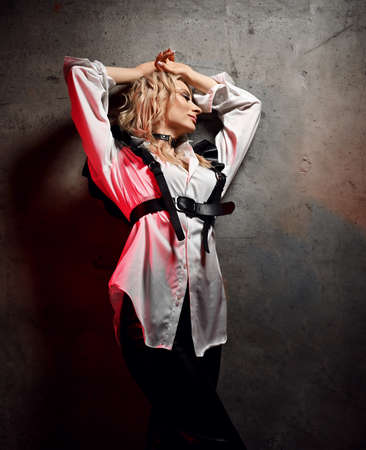 Sensual blonde woman in leather pants, white shirt and leather belts stands at concrete wall, hands up, feeling pleasure