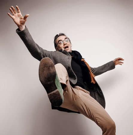 Astonished adult man in pants and plaid jacket stands holding foot up, making giant step, falling down waving hands Stok Fotoğraf