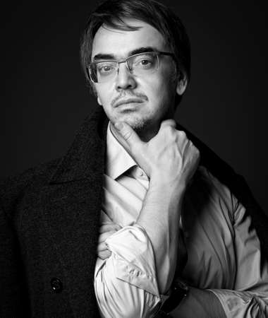 Black and white portrait of adult man literary critic, poet, writer in white shirt and teed jacket on shoulders